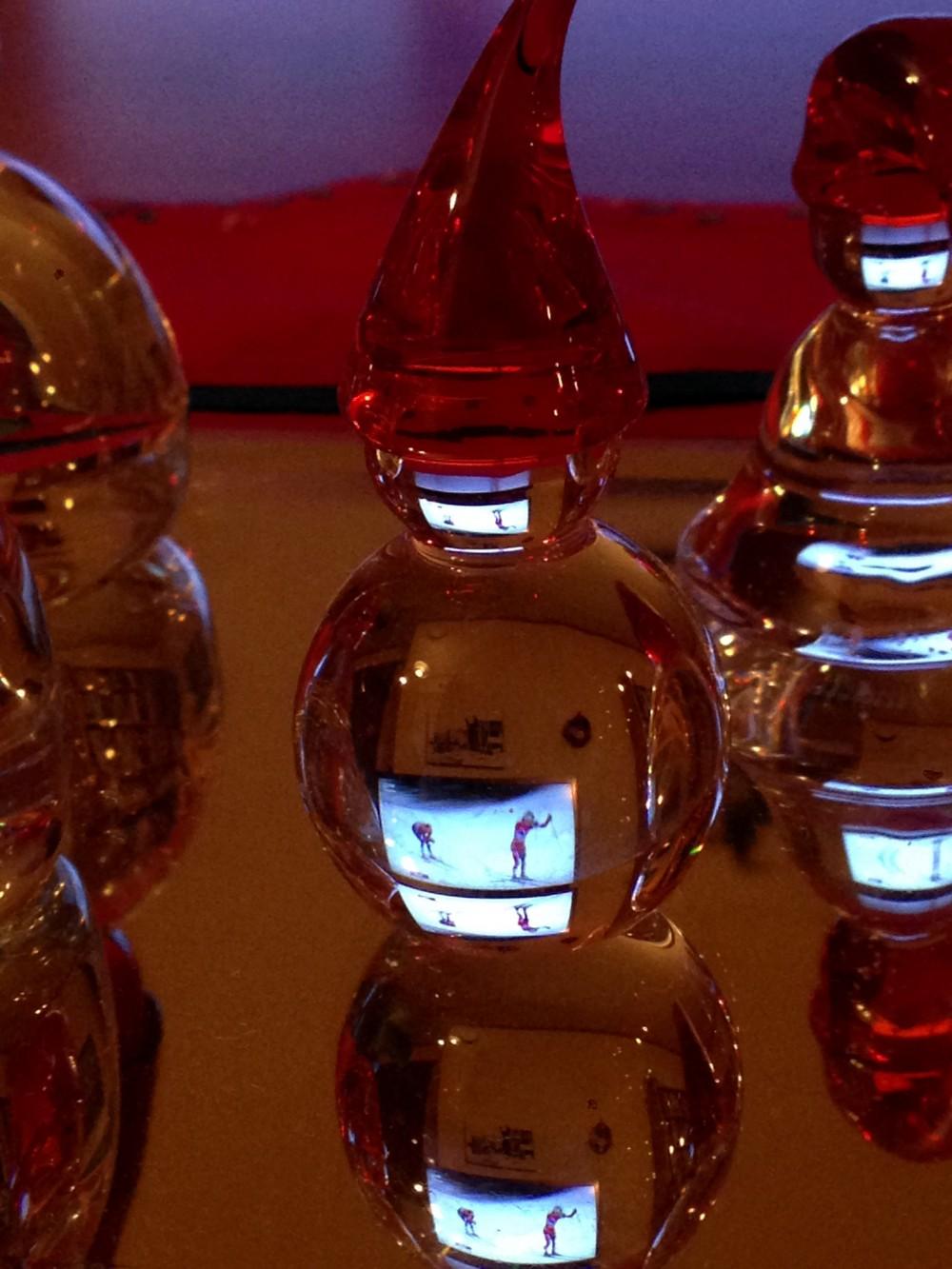 NRKs sportssending reflektert gjennom noen glassnisser på et bord
